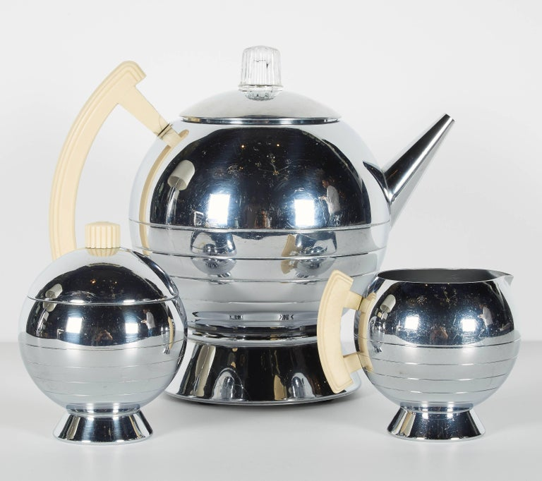 Iconic Art Deco coffee and tea service set with stylized Machine Age design. All pieces have chrome finish with bakelite handles and accents in ivory and cognac. The serving set includes an electric coffee pot, sugar, creamer, serving tray, and