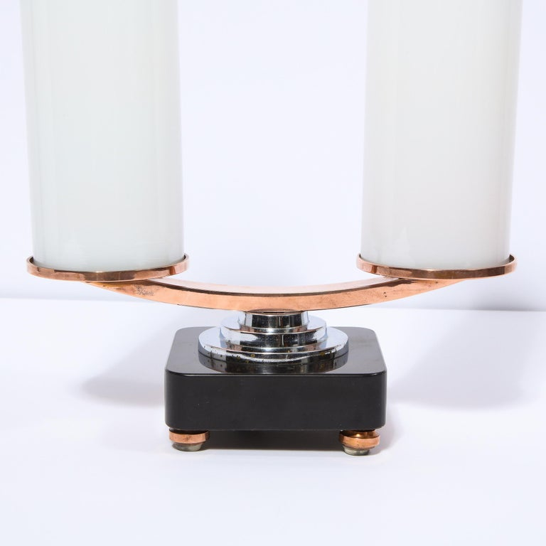 This stunning Art Deco Machine Age skyscraper style streamlined table lamp was realized in the United States, circa 1935. It features a volumetric square vitrolite glass base with rounded corners and round skyscraper style chrome & copper feet. A