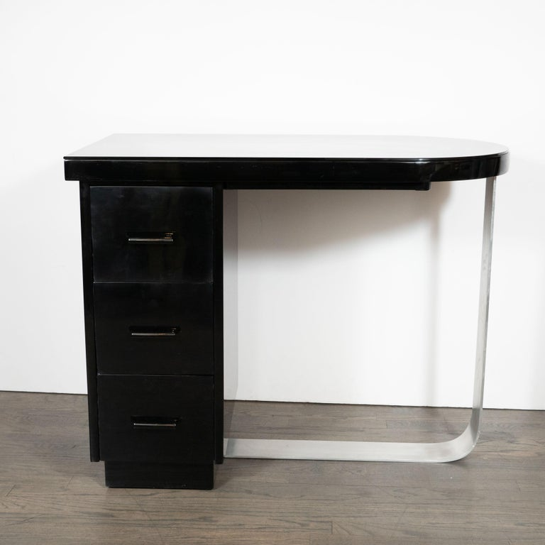 This elegant Machine Age Art Deco desk was realized in the United States, circa 1935. It features a streamlined black lacquer top (fitted with a layer of protective black glass) suggesting a stylized bullet- a form that manifests the period's