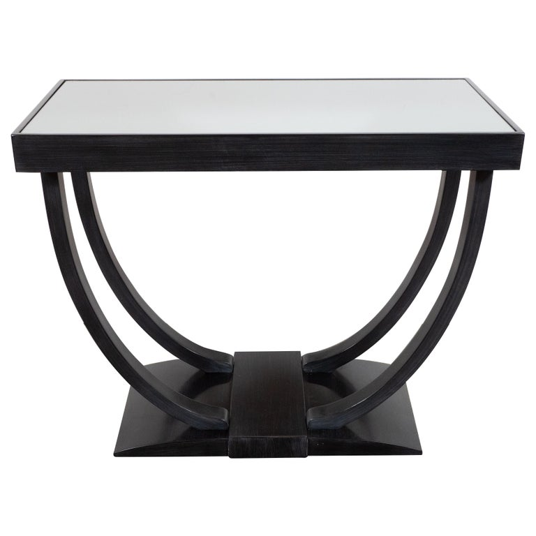 This elegant Art Deco Machine Age table was realized in the United States, circa 1935. It features a subtly domed base with a raised rectangular embellishment in the center from which two concave streamlined rectangular supports ascend. The supports