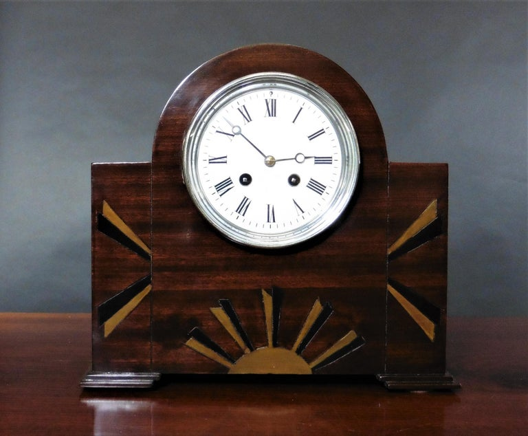 Art Deco Mahogany Mantel Clock    Art Deco mahogany mantel clock housed in a break arch case with geometric fan inlay standing on block feet.  Chrome bezel opening to an enamel dial with Roman numerals and original 'blued' steel