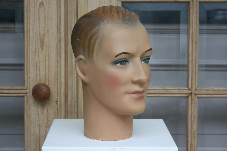 The mannequin head of a young man dates back to the 1930s of the 20th century and is made of plaster. It is painted polychrome. The man is wearing makeup and has painted eyes.  Dimensions: 31 cm high / 12.2 inch high, 17 cm wide / 6.69 inch