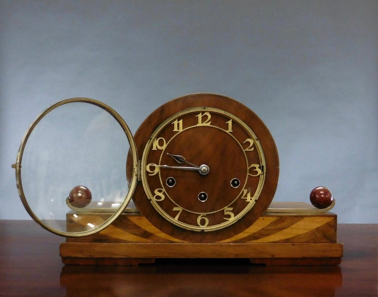 Art Deco mantel clock   Art Deco mantel clock standing on a stepped walnut base with boxwood inlay, chrome and sphere decoration to either side of the chrome bezel.  Silvered, skeletonised chapter ring with Arabic numerals and original chrome