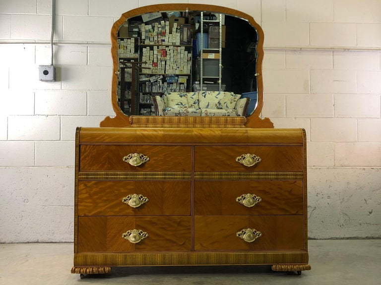 Art Deco Waterfall-style six drawer dresser with matchbook veneer and zebra wood accents. The dresser has solid brass pulls and is on castors. The mirror back also has the zebra wood accents. Excellent refinished condition. No marks. Dresser only