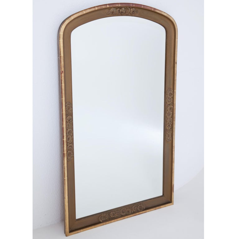 Large wall mirror in Art Deco style. The rounded frame with relief floral decoration. Wood, partly gold patinated.