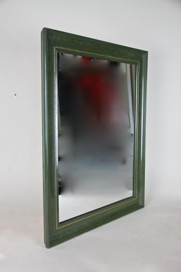 Timeless Art Deco mirror from Austria, circa 1930. The lacquered frame shows a beautiful olive green surface. This straight designed wall mirror was additionally decorated by an inlayed brass strip. Unfortunately the original mirror glass was