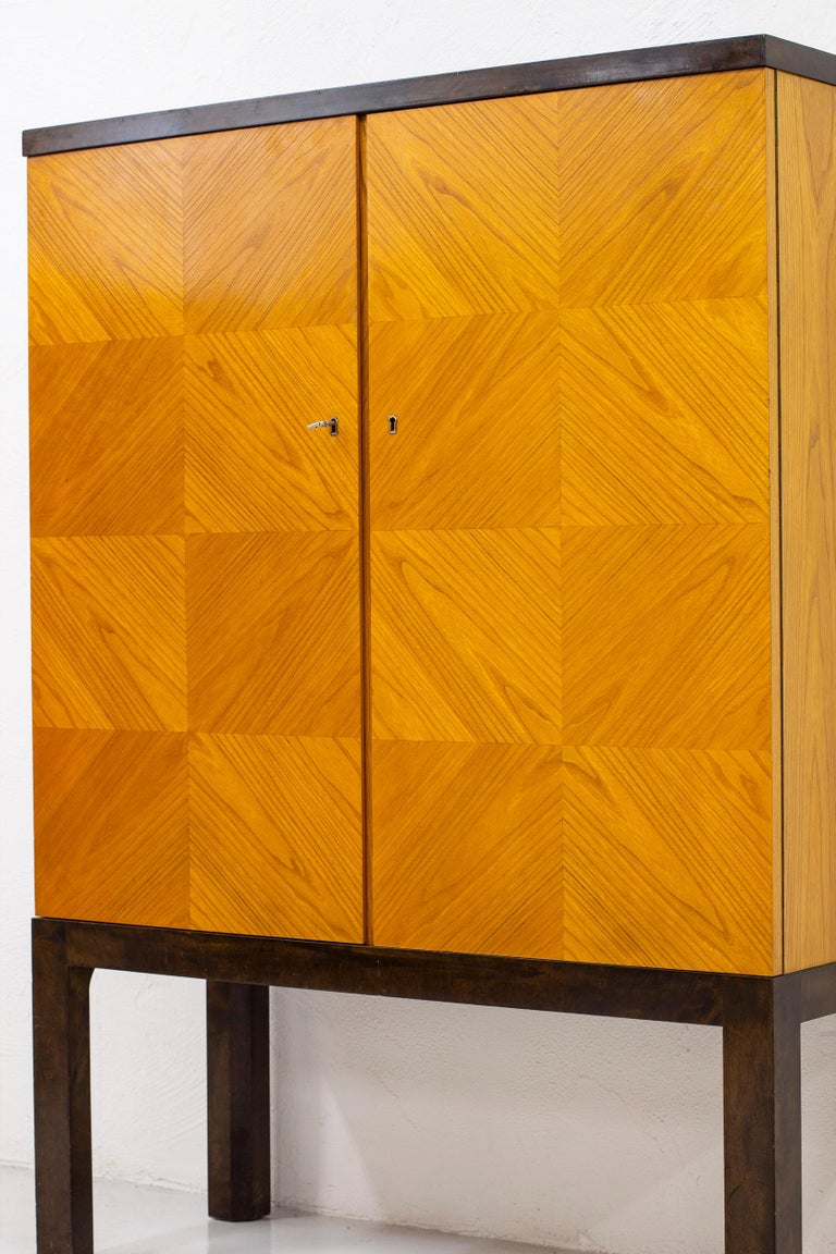 Modernist/Art Deco cabinet in the style of Otto Schulz. Produced in Sweden by unknown cabinetmaker during the 1930s. Stained birch legs and top with doors veneered in a checker board pattern in elm wood. Inside of the cabinet veneered in oak with