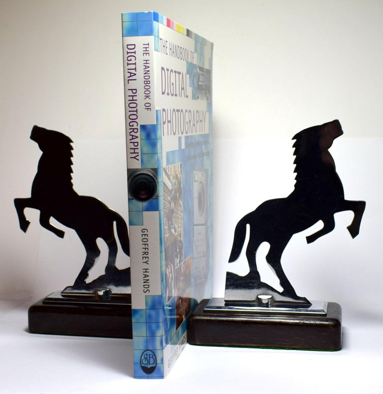 Very stylish and rare two dimensional bookends depicting two rearing stallions. Both are totally authentic and originate from the 1930s. These fabulous Art Deco bookends rest on a mahogany hard wood base. The chrome and the bases are in mint