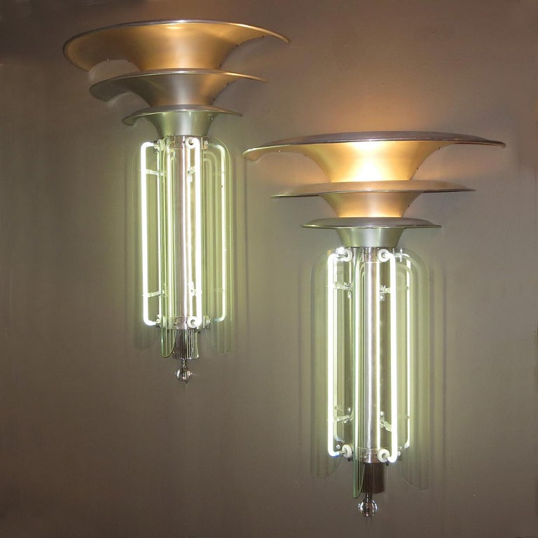 These wonderful sconces were originally from a Chicago area 1930s theatre. They utilized the most modern of materials and design, including bands of etched glass intersected with neon tubes. We have done a sensitive restoration to the lamps. The