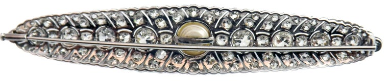 This wonderful Art Deco platinum diamond and natural freshwater pearl brooch was meticulously handcrafted in ca. 1930. The perfectly matched Old European cut bright white and lively diamonds were finely set in a geometrical pattern indicative of