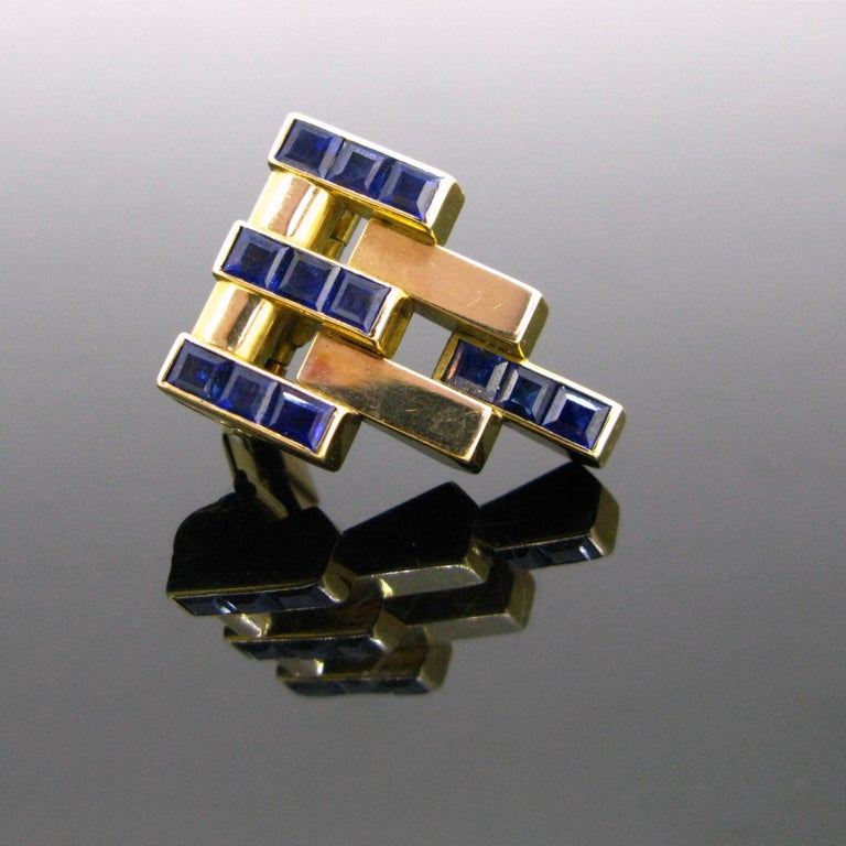 This ravishing clip comes directly from the Art Deco era, circa 1925. It has a geometric design, 4 lines are set with 3 calibrated naturals sapphires. They have a deep blue colour. The yellow gold is smooth and shiny. The back is engraved: ME PE WO