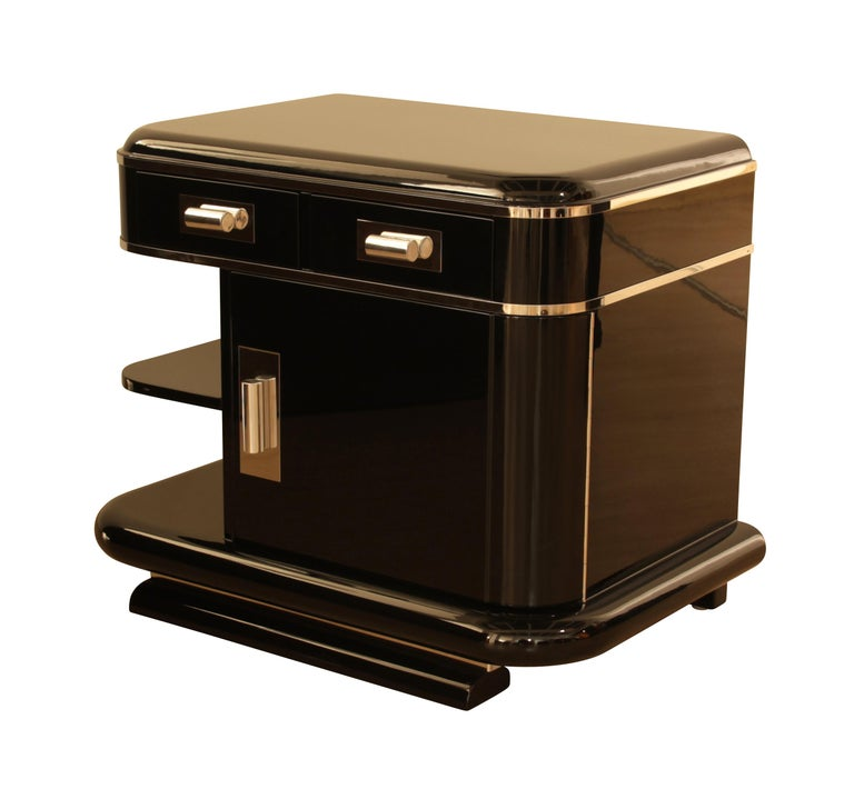 Wonderful pair of elegant Art Deco nightstands or bedside tables.  2 drawers, 1 door and 2 open shelves.  The walnut wood has been elaborately lacquered and polished in black (piano lacquer).  On the inside it is walnut veneered and also