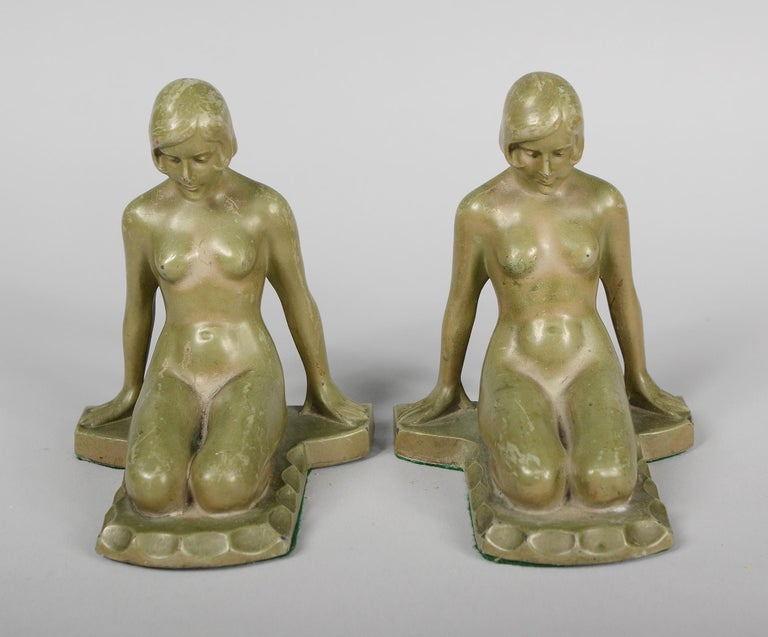 Art Deco bookends with a kneeling nude woman. These are spelter with green paint. These have very good detail in the figures. There are some paint losses overall. One has a casting flaw between the leg and base.