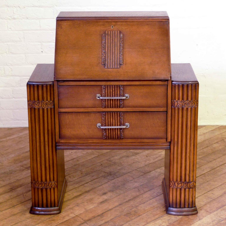 An Art Deco oak bureau of unusual design, with side bookcases. The fluted side pilasters are slightly bowed, typical of the Art Deco period as are the applied carvings to the fall and drawer fronts. Nice to see the original steel handles and working