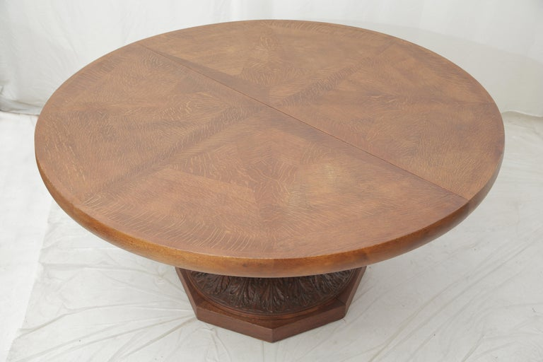 Large round dining table from the late French Art Deco period made of oakwood. Extensions are possible and can be added. Interesting design with a star shape on the top veneer of the table, elegantly carved with plant representations all around the