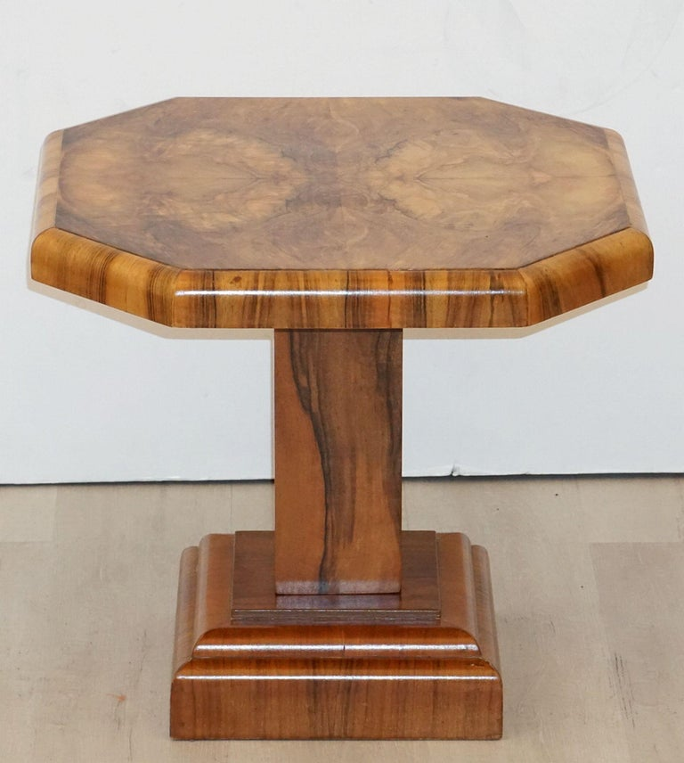 A fine English side table or occasional table from the Art Deco period, circa 1935, featuring an octagonal table top over a square walnut pedestal support and raised base. The whole with lovely figured veneers of burled walnut.
