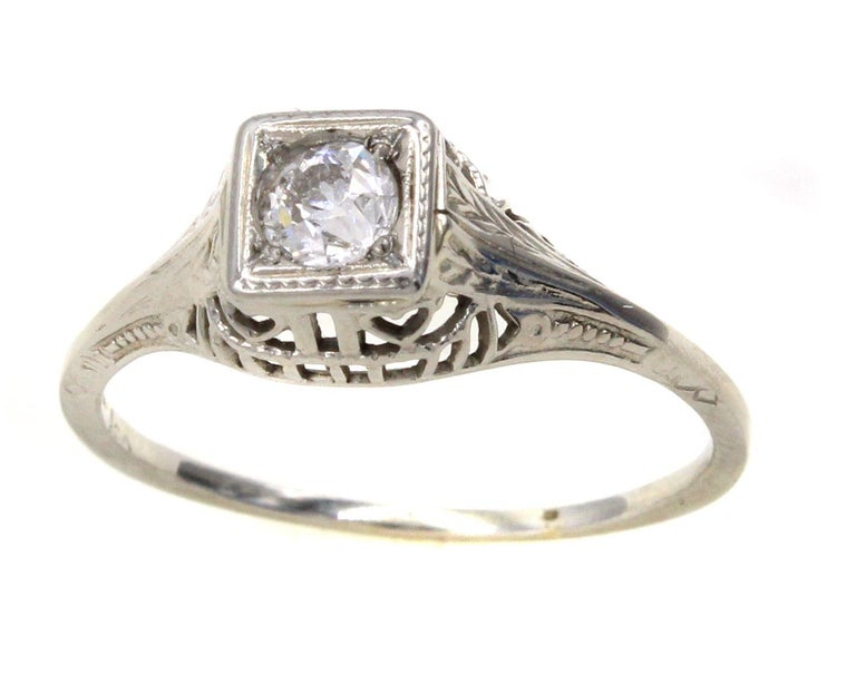 This well handcrafted Art Deco 18 Karat white gold engagement ring is centrally set with a bright white Old European cut diamond measured to weigh approximately 0.30 carats. The gallery is has beautiful a-jour work and fine hand engraving. A