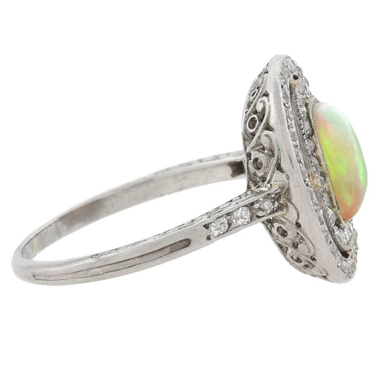 A stunning opal and diamond ring from the Art Deco (ca1920s) era! This fabulous piece is crafted in platinum and features a lovely opal cabochon bezel set at its center. The opal has an alluring quality and a vibrant multitude of colors that vividly