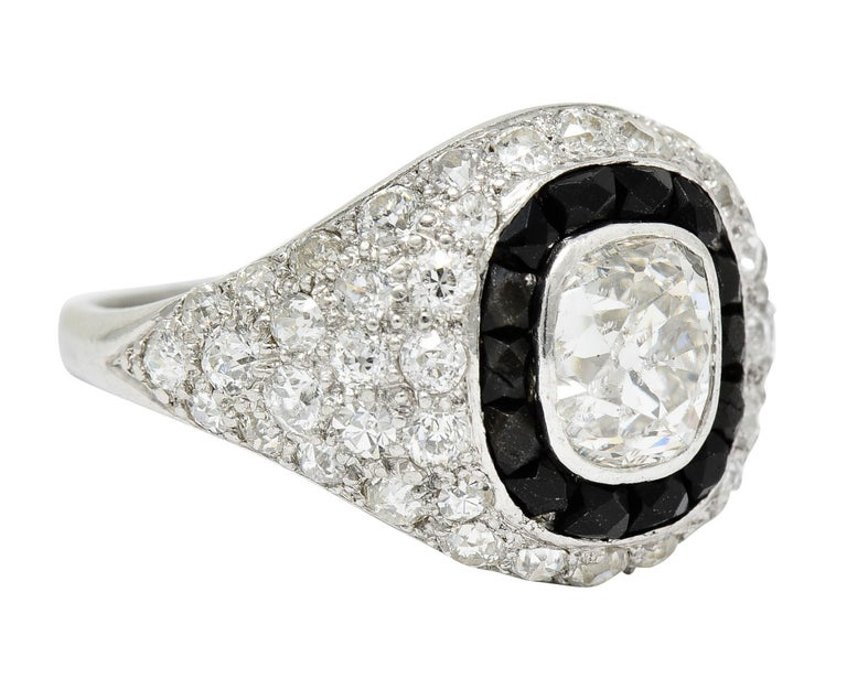 Centering an old mine cut diamond weighing approximately 1.00 carat - J color with SI2 clarity  Bezel set and surrounded by a calibrè cut onyx halo - faceted, opaque black, with very good polish  Pavè set throughout by old European and single cut