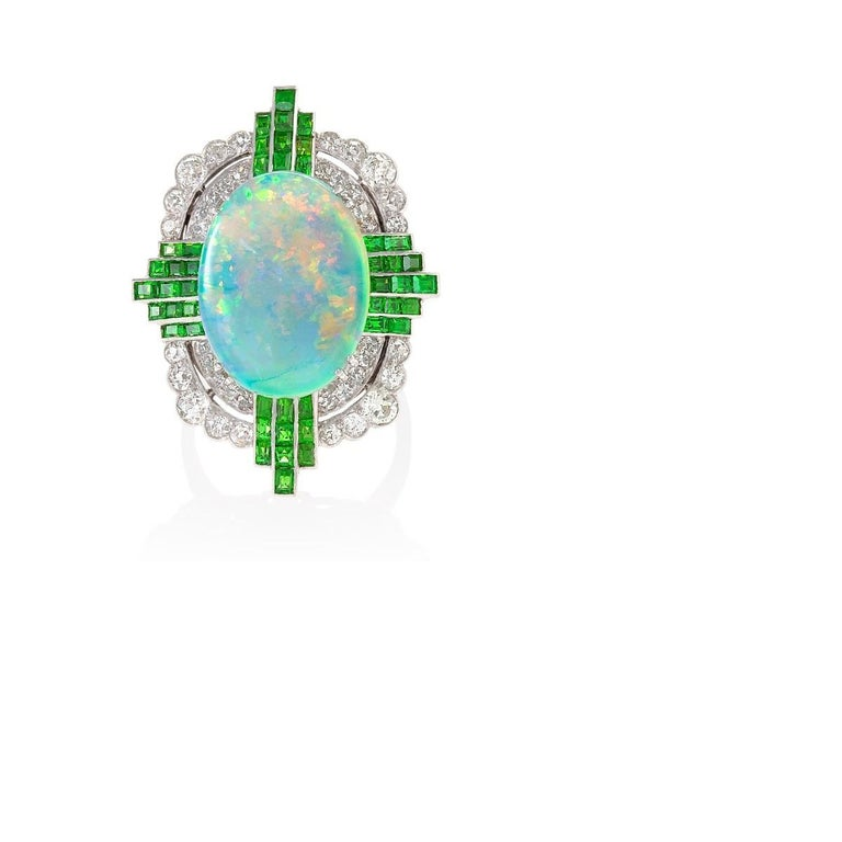 An Art Deco platinum ring with white opal, demantoid garnets and diamonds. The ring centers on a white opal that has an approximate weight of  3.77 carats. It is surrounded by  47 calibre-cut demantoid garnets with an approximate total weight of