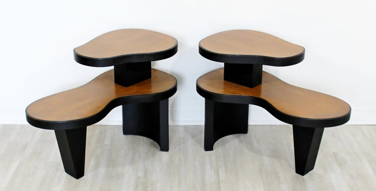 For your consideration is a magnificent pair of two tiered, Art Deco, amoeba shaped wood side or end tables, circa 1940s, in the style of Gilbert Rhode or Donald Deskey. In very good antique condition. The dimensions are 29