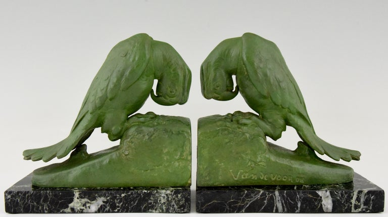 A pair of Art Deco parrot bookends by Georges van de Voorde, Belgian artist who worked in France. Signed and with founders' seal. Lovely green patina, mounted on green marble base, ca. 1925.   There is a picture of these bookends on page 328 in