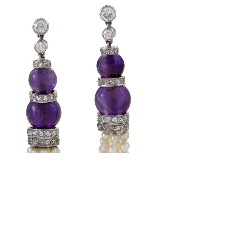 A pair of Art Deco platinum earrings with diamond, amethyst  and natural pearl tassels. The natural pearl tassel earrings are topped with 4 amethyst beads and 112 Old European-cut diamond-studded roundels that have the approximate total of 1.64