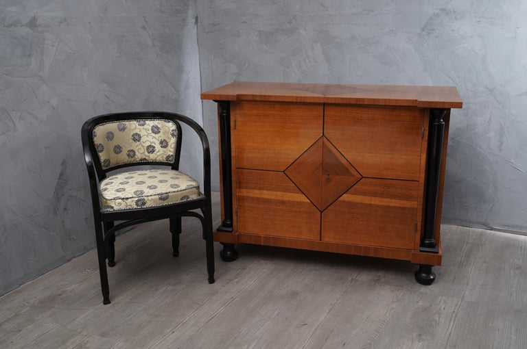 Demilune sideboard, a beautiful patina characterizes the pear wood grain, enhanced by columns and feet lacquered in black shellac.   Art Deco Austrian sideboard, all veneered in pear wood, with special threads in ebonized wood in the front part.