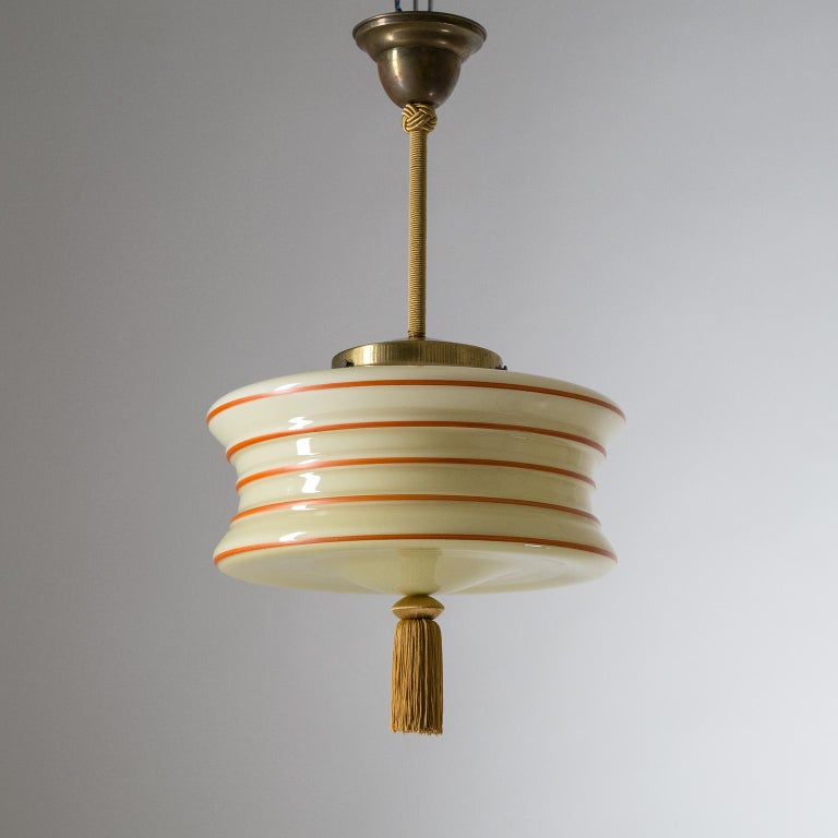 Enameled glass pendant from the 1930s. The uniquely shaped glass diffuser is made of Ivory tinted glass with a white inner casing and red hand-painted lines, emphasizing the structured silhouette. Brass hardware with covered stem and a tassel at the