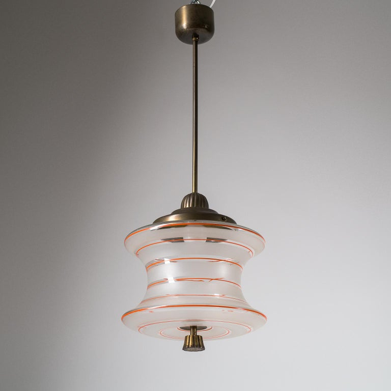 Unusually shaped glass pendant or lantern from the 1930s. The concave shaped blown glass diffuser has broad etched stripes with intermittent hand painted thin red lines. The hardware is brass with the bottom finial in brass plated steel. Fine