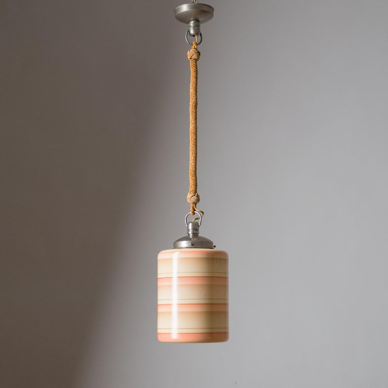 Rare Art Deco pendant or lantern, circa 1930. Suspended by a twisted cord is a cylindrical ivory-colored glass diffuser enameled with alternating stripes and gradients. Fine original condition with some light patina on the nickeled brass hardware.