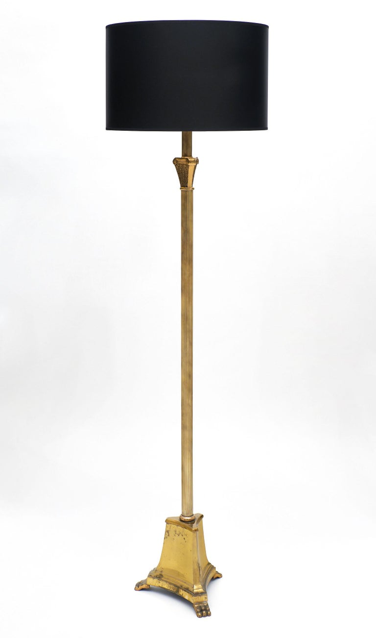 French Art Deco period floor lamp made of gilded brass and featuring a stylized tripod base with claw feet. We love the stylized Corinthian capital. It has been newly wired to fit US standards.