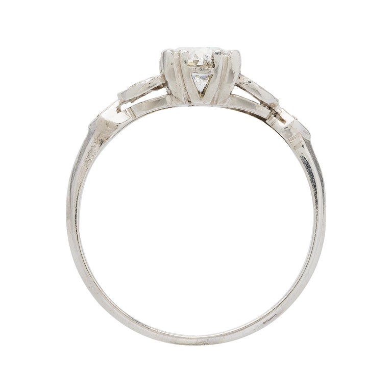 This is an amazing Art Deco platinum engagement ring centering a 0.88ct Old European Cut diamond graded J/K color color and VS clarity. This Art Deco mounting is designed to follow the shape of your finger perfectly. The trio of marquise-shaped
