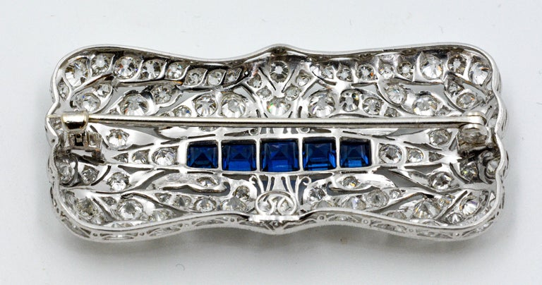 Early mid-century Art Deco Platinum brooch set with 5 synthetic blue Sapphires of approximately 2.0 carats. Artfully accented with approximately 102 round brilliant cut diamonds weighing approximately 4.0 carats (I-J color, SI internal clarity).