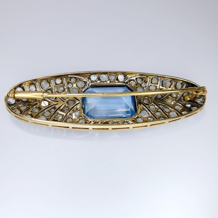 This beautiful Art Deco Brooch in oval shape has a center blue colored stone in emerald cut. the old cut diamonds rest in band of spikes on platinum base and reverse of 18k rose gold   READY TO SHIP *Shipment of this piece is not affected by