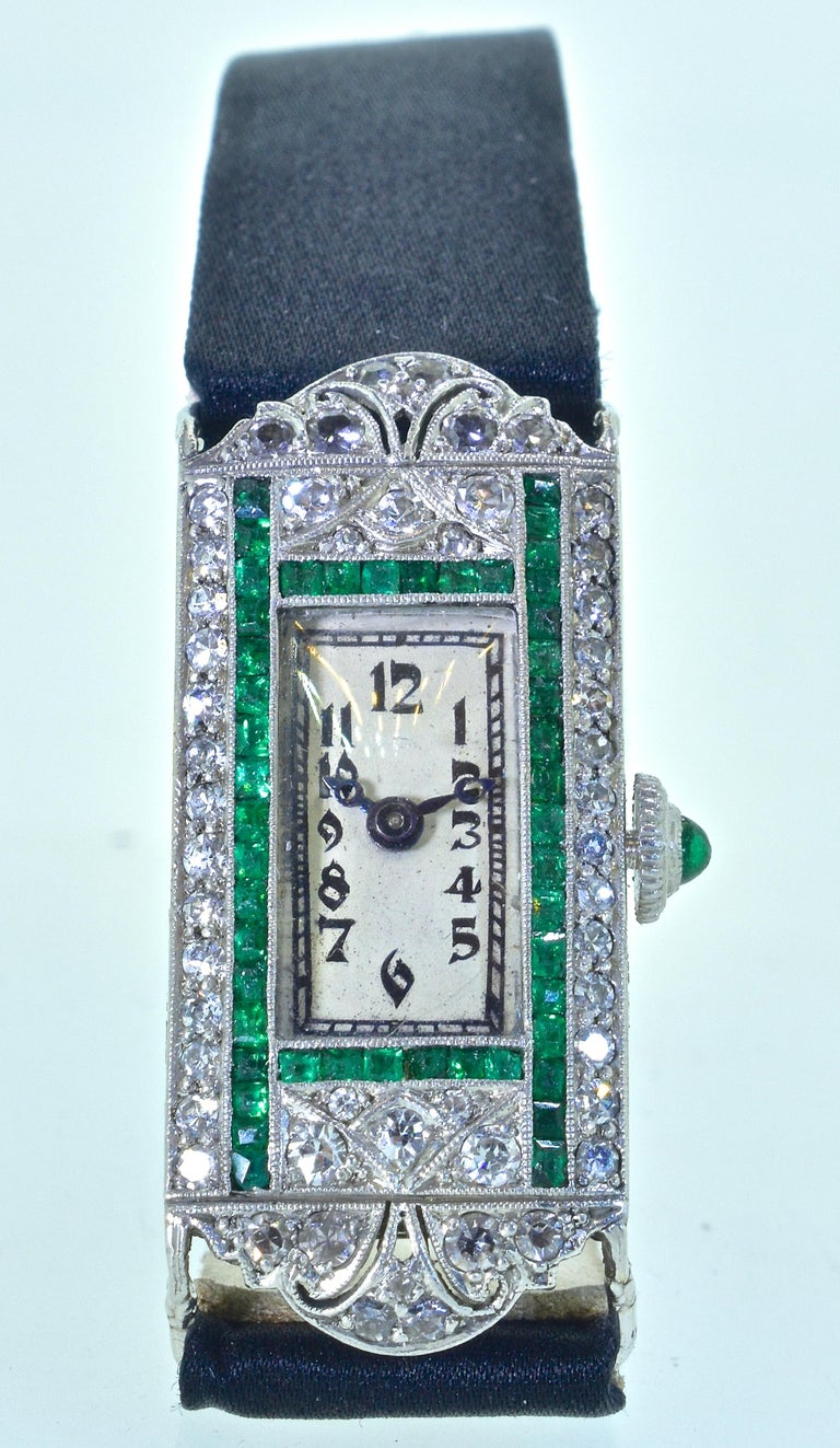 Art Deco wristwatch composed of diamonds and calibre cut emeralds.  In platinum with highly engraved sides, this wristwatch which is in fine condition, recently serviced, and guaranteed for a year.  The movement is by Cart. A fine Swiss watch maker.