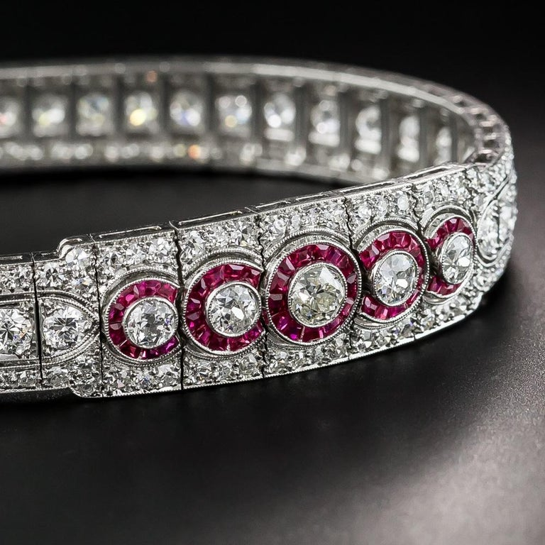 Exquisite, unique and stunning well describes this premier and pristine original Art Deco bracelet, masterfully hand fabricated in platinum at the peak of the Jazz Age - circa 1925. Centering on five overlapping (synthetic) ruby-haloed diamonds
