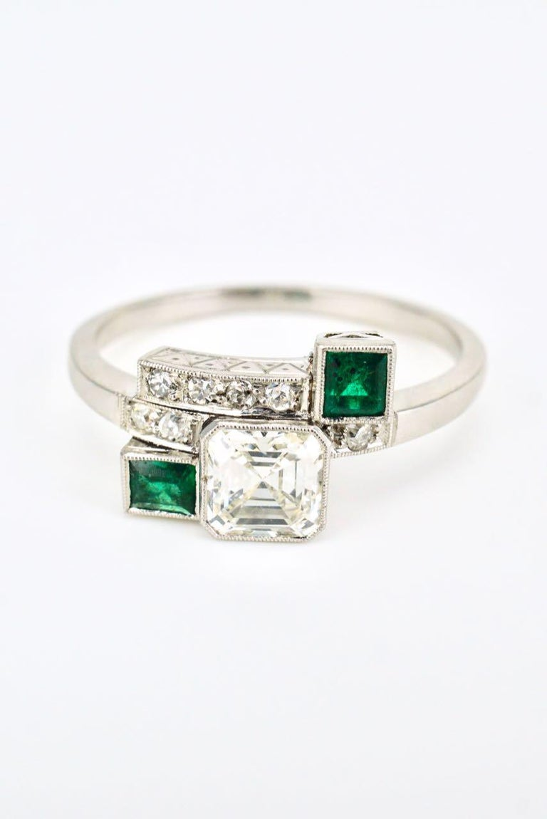 An Art Deco platinum diamond emerald abstract ring.  A very unique ring design featuring an emerald cut diamond bezel set in a cluster between two asymmetrically placed emerald cut emeralds and 7 single cut diamonds on a tapered square shank  -