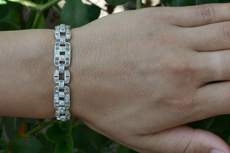 The Huntington Art Deco Filigree Diamond Bracelet. Measuring an eminently wearable 3/8 inch wide, this chic and stunning Jazz Age jewel, circa 1910s-1920s, is designed with alternating triple-row sections, each set with 4 gems and connected by