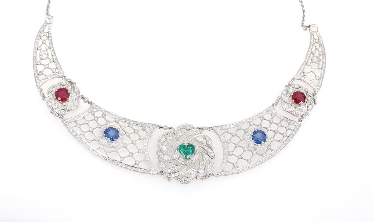 Almost 2Ct each, Emerald centre stone heart-shaped, two natural high-quality Sapphires and two Rubies surrounded by Diamonds. Platinum.  Two natural high-quality Sapphires and two Rubies on the sides make the composition perfect.  Almost a full