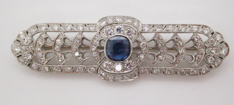 This absolutely breathtaking bar pin puts on display the best of the Art Deco era in the form of a stunning hand-pierced, open architectural design featuring dozens of bright white diamonds and a killer no heat blue sapphire center. The sides of the