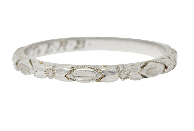Band style ring deeply engraved with an arbutus flower motif that alternates with a concave navette form  Profile features geometric motif, fully around  Accented throughout by milgrain detail  With inside inscription, signed Arbutus, and maker's