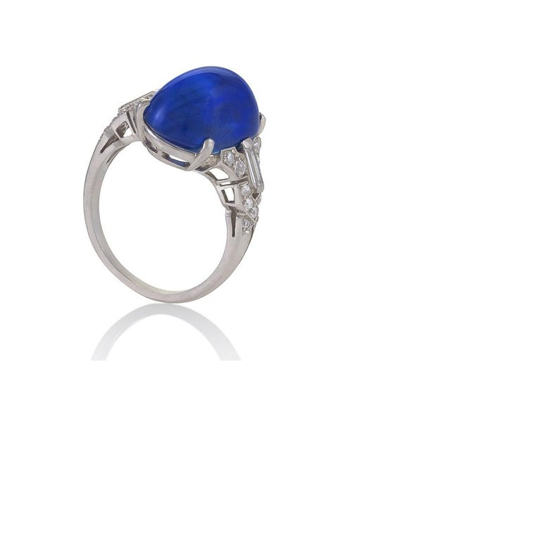 An Art Deco platinum-set diamond and sapphire ring. The ring prominently features a cabochon untreated Ceylon sapphire of 15.36 carats that has an AGL certificate. Twenty-two round diamonds and 2 beautiful baguettes accent the shank in an