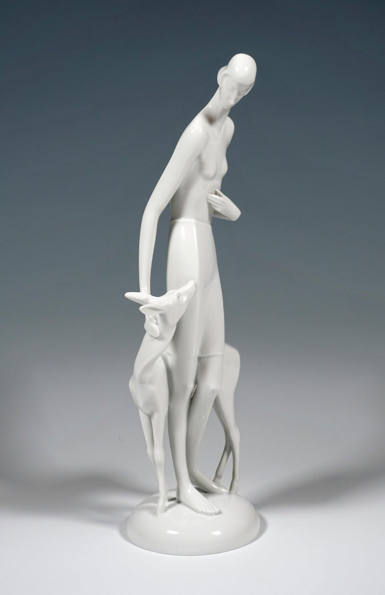 Manneristly elongated young woman, stroking a deer, clad only in a knee-length skirt. On a cambered, round base.  Designed by Gerhard Schliepstein (1886 - 1963), German sculptor and designer of Art Deco as well as a porcelain modeller. Until the