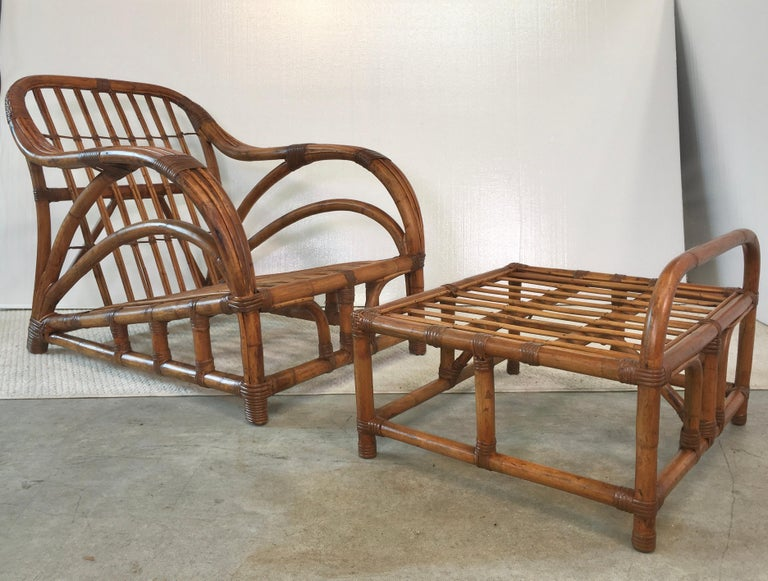 Sleek, streamlined and generously proportioned 1940s Art Deco rattan roadster lounge chair and ottoman. Big chair for a big man. Note how beautifully the three tubular strands of the arms flow sinuously into the arched back of the chair. Solid,
