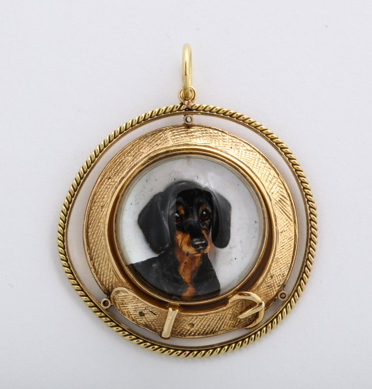 On a background of mother of pearl, popping forward as if ready to jump on your lap, a black and tan dachshund looks at you with soft eyes that seem to implore you to remain at home. We all know that look that makes you feel guilty about leaving.