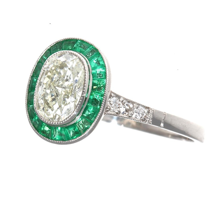 A design driven by colorful passion giving devotion to the art deco time period. Featuring a 1.01 carat oval cut diamond that is L color, SI1 clarity. Brilliantly surrounded by a vibrant green halo of calibrated emeralds specially cut to mirror the