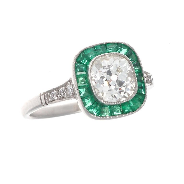 A creative and singular way of saying I love you. Featuring a 1.22 carat old mine cut diamond brilliantly surrounded by a vibrant green halo of calibrated emeralds, specially cut to mirror each facet of the diamond. Hand crafted in platinum. Ring