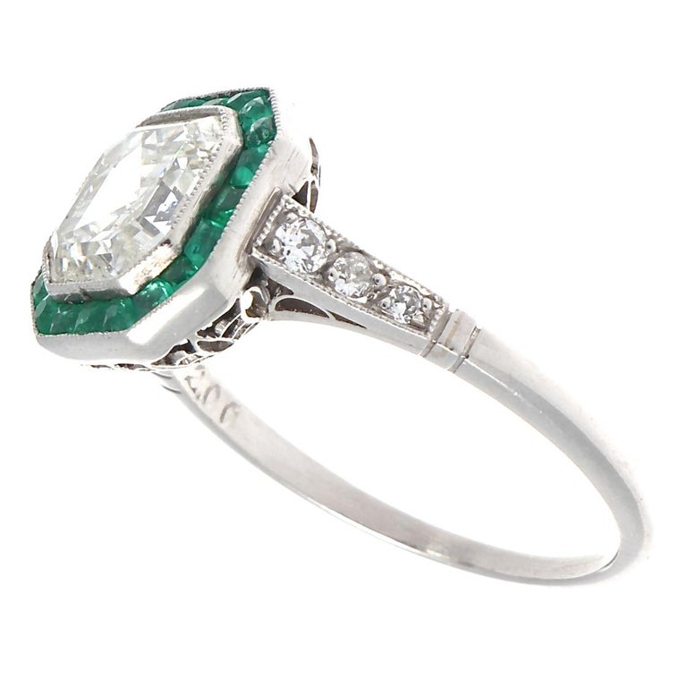 Stunning Art deco inspired ring featuring an elegant 2.00 carat Asscher cut diamond. Not only pleasing to the eye but easy on the pocketbook for such an outstanding ring. We grade as J-K color, VS2-SI1 clarity.  Accented with calibré cut emeralds,