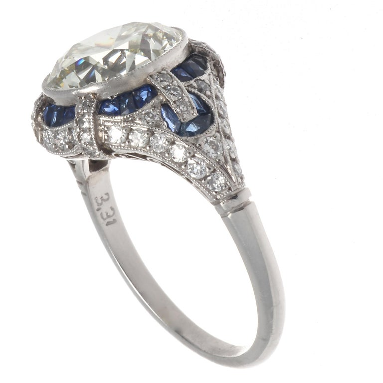 An Art Deco inspired diamond sapphire platinum engagement ring displaying symmetry, style and elegance. Featuring a 3.31 carat old European cut diamond, graded K-L color, VVS clarity. With 24 French cut sapphires that weigh approximately 1.00 carat,